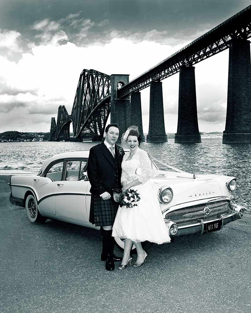 wedding photographer couple sit on vintage car by forth road bridge