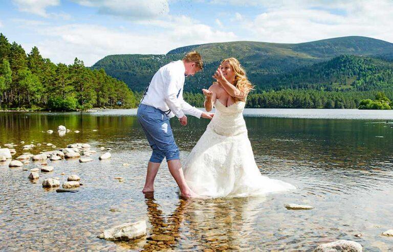 wedding photographer in scotland, couple frolick in Loch an Eilein