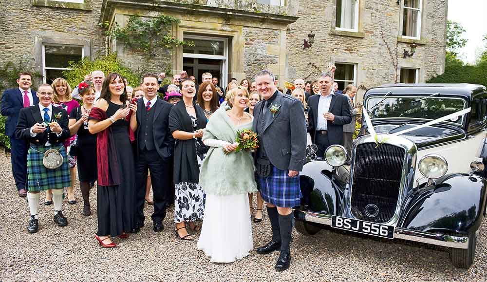 wedding photographer photo of couple and guest cheering outside manor house