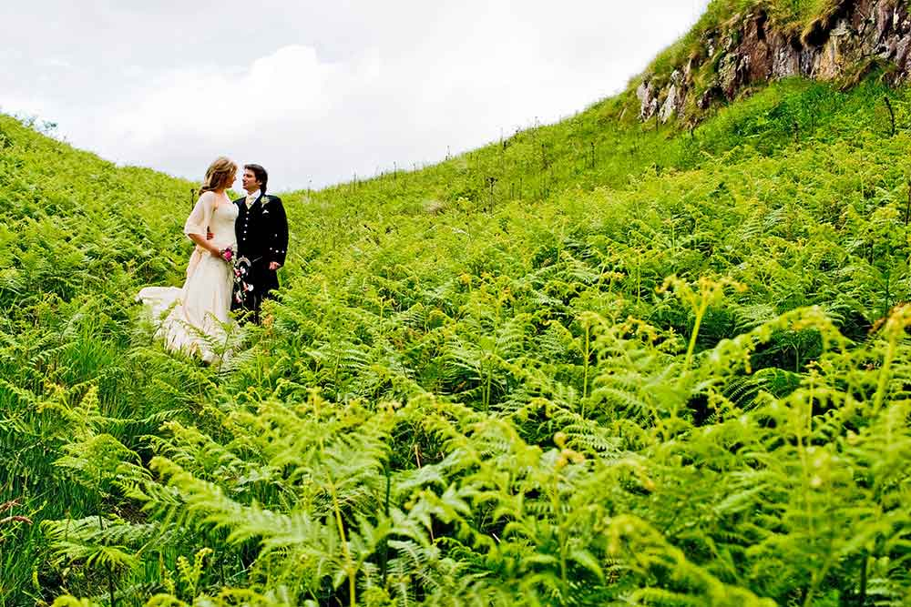 couple embrace surrounded by green ferns