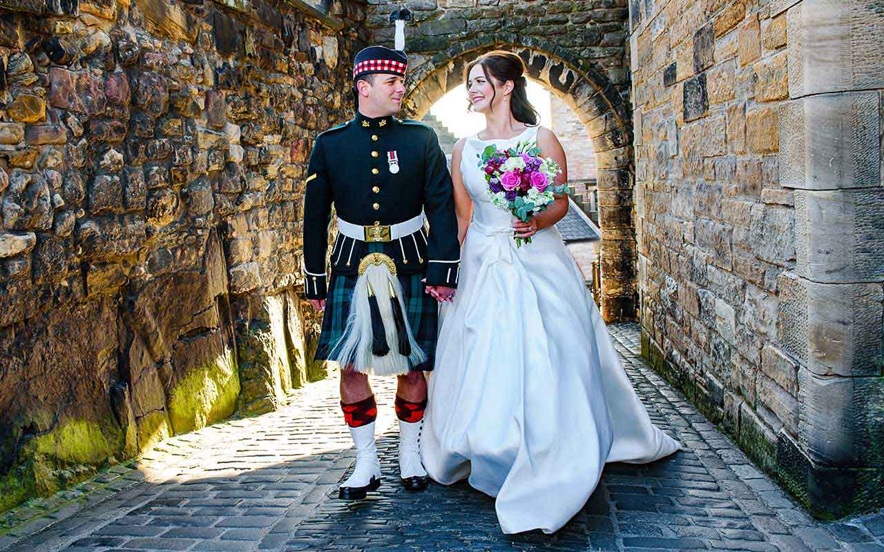 groom in military dress with bride walk on cobbled path