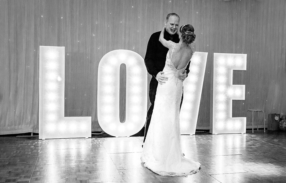 stylish photo of wedding couple first dance with love sign in background