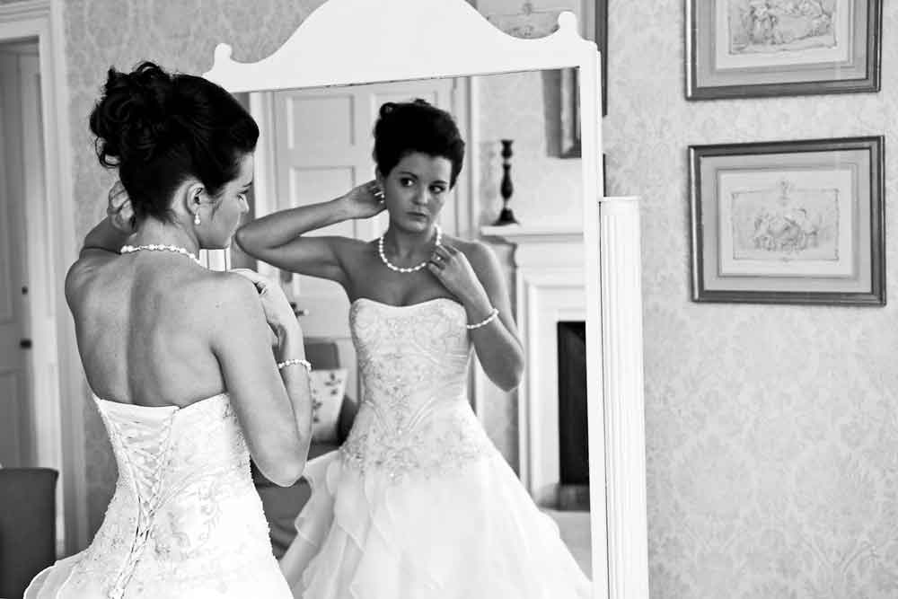 wedding photo bride prepares looking in mirror