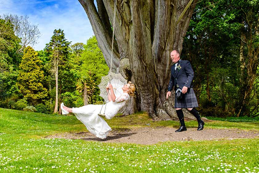wedding couple - bride with parasol on swing, groom pushing