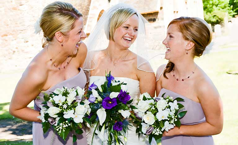 bride and bridesmaids laugh together