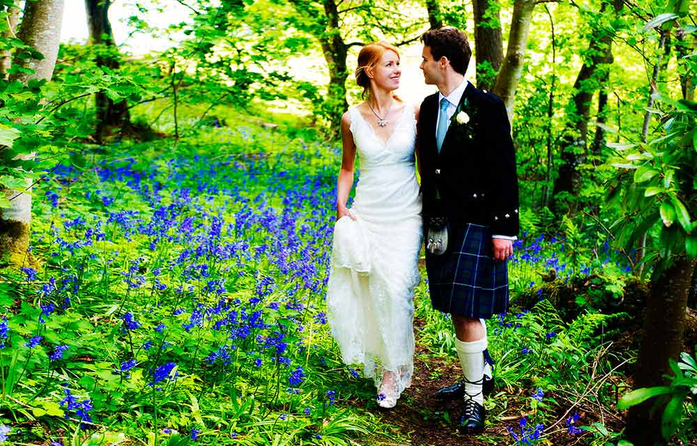 wedding couple walk through bluebell wood