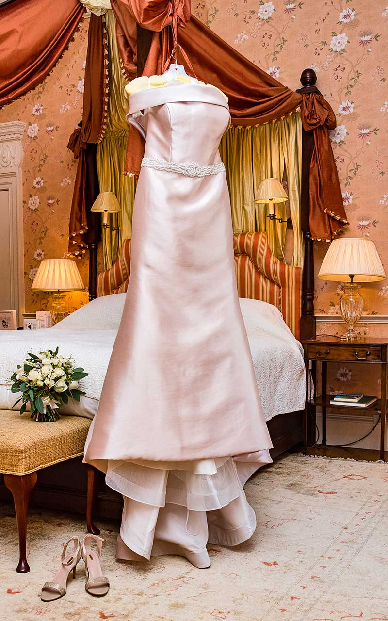 wedding dress hung on four poster bed