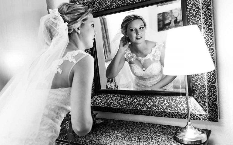 bride prepares looking in mirror