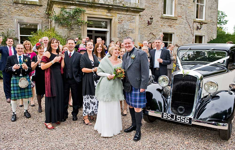 wedding photographer couple and guests by vintage car