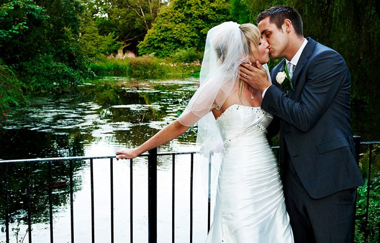wedding photographer couple kiss by lily pond