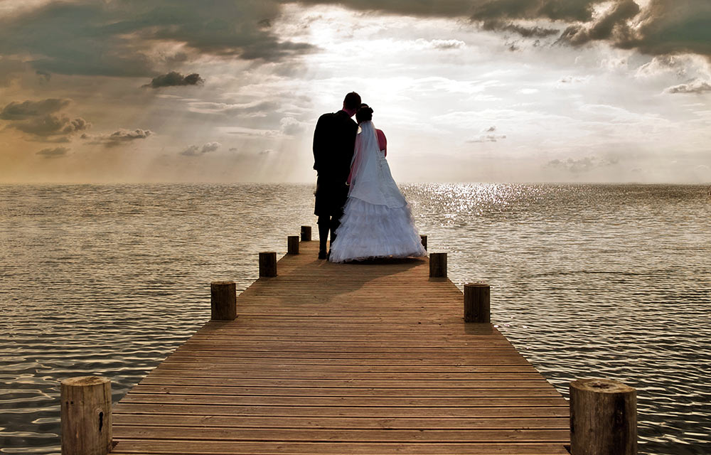 wedding photographer couple view sunburst from pier