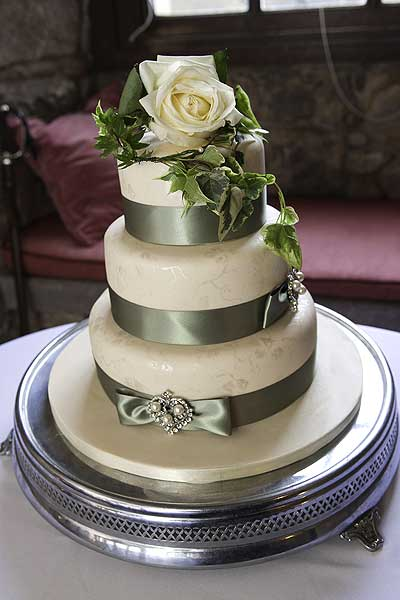 wedding cake with sage green ribbons