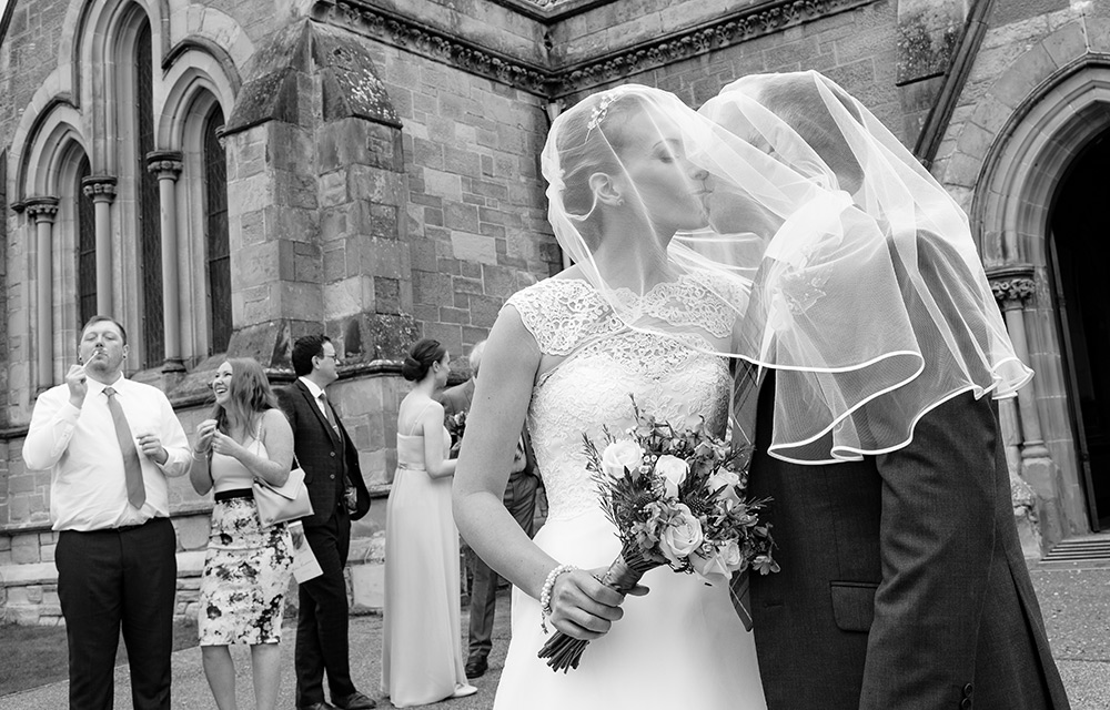 couple kiss under brides veil
